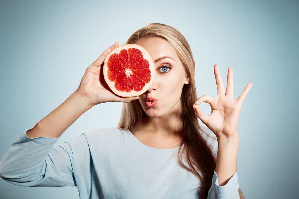 Young blonde woman with grapefruit in her hands studio portrait isolated on blue background. Young blond woman showing OK sign about the benefits of vitamin C